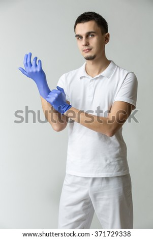 Male doctor in white uniform wears blue latex gloves. He looks to the camera on the gray background. Studio photo. Vertical. - stock photo