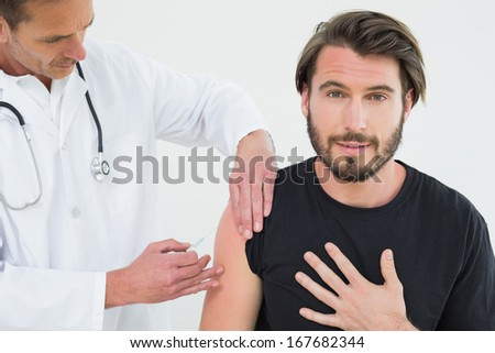 Male doctor injecting a young male patient's arm over white background - stock photo