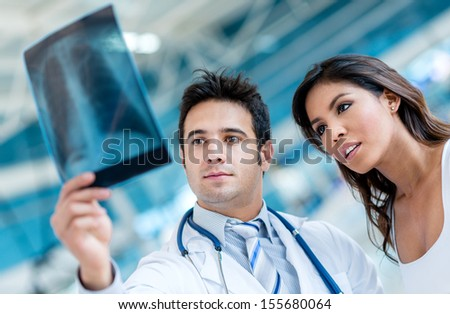 Male doctor looking an x-ray  with a patient  - stock photo