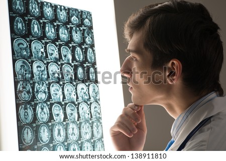 male doctor looking at the x-ray image attached to the glowing screen - stock photo