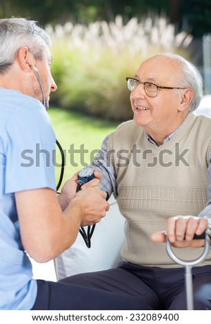 Male doctor measuring blood pressure of elderly man at nursing home - stock photo