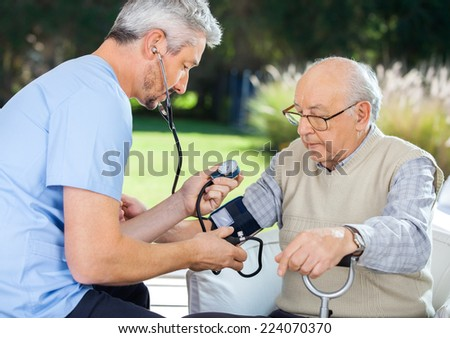 Male doctor measuring blood pressure of senior man at nursing home - stock photo