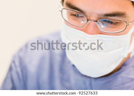 Male doctor operating in the surgery room - stock photo