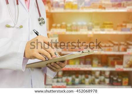 male doctor ,pharmacist with stethoscope holding clipboard and writing a prescription, at the hospital order medicine by pharmacy,Healthcare and medical concept,selective focus - stock photo