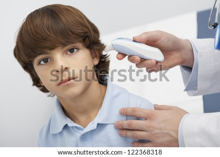 Male doctor's hand checking patient with digital thermometer - stock photo