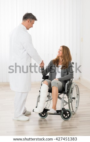 Male Doctor Shaking Hands With Patient Sitting On Wheelchair