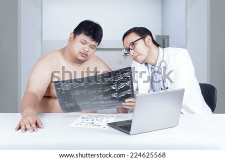 Male doctor showing and explaining the scan result of backbone to overweight patient - stock photo