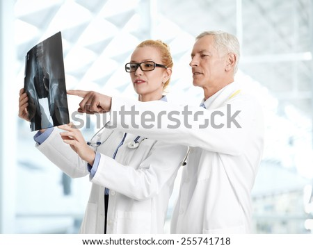 Male doctor shows the problem areas on a X-ray to his colleagues at private clinic.  - stock photo
