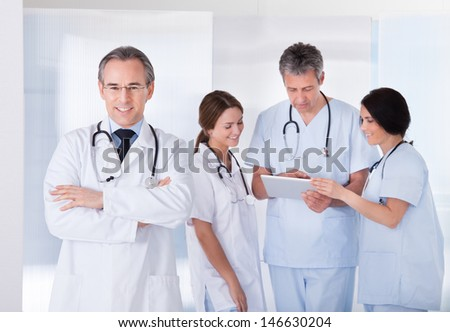 Male Doctor Standing In Front Of Team Using Digital Tablet - stock photo