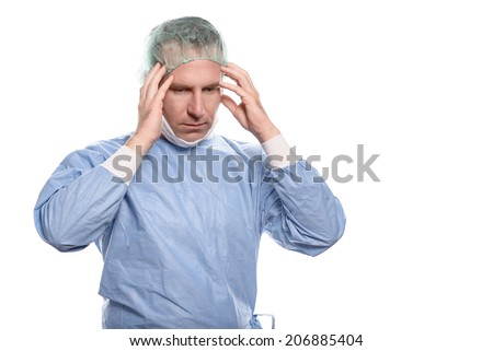 Male doctor suffering from a headache and fatigue holding his temples with his hands and eyes closed as he grimaces in pain - stock photo