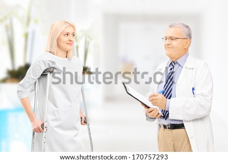 Male doctor talking to female patient with crutches in hospital corridor