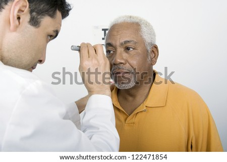 Male doctor testing patient's eye in clinic - stock photo