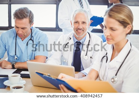 Male doctor using laptop in conference room and colleagues working beside him