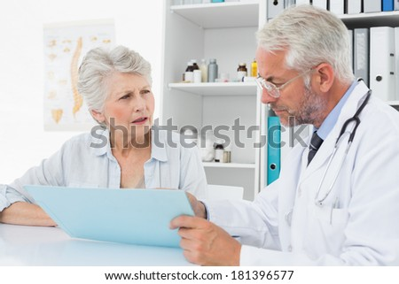Male doctor with female patient reading reports at medical office