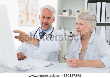 Male doctor with female patient reading reports on computer at medical office - stock photo