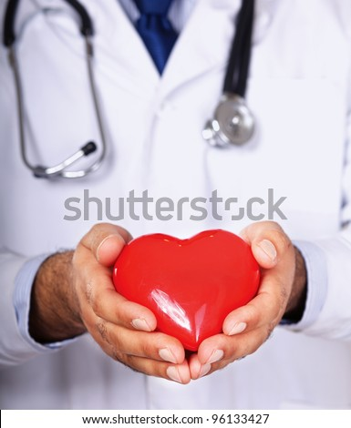 Male doctor with stethoscope holding heart - stock photo