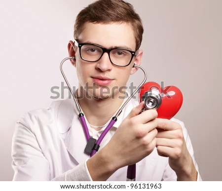 Male doctor with stethoscope listening heart on white background.