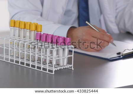 Male doctor write on the desk with test tube. - stock photo