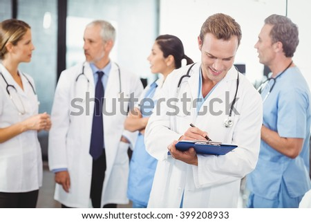 Male doctor writing on clipboard and colleagues standing behind and discussing in hospital