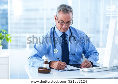 Male doctor writing prescription white sitting at desk in hospital - stock photo