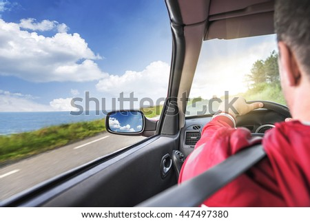 Male driver drives a convertible car on the country road by the sea. The view from the cabin, rear view, inside.