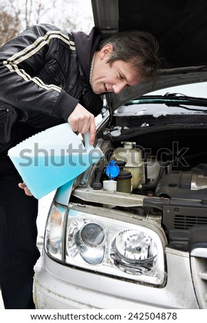 Male driver fills antifreeze liquid in the washer window