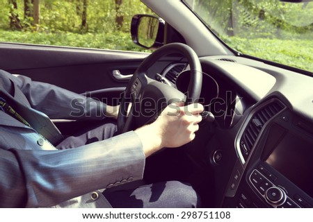 Male driver hands holding steering wheel