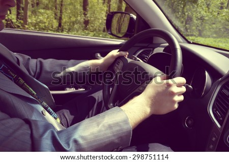 Male driver hands holding steering wheel - stock photo