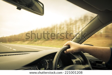 Male driver hands holding steering wheel of a car and road - stock photo