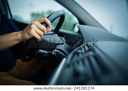 Male driver's hands driving a car on a highway (color toned image; shallow DOF) - stock photo