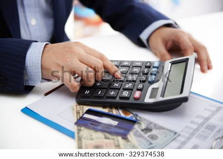 Male economist working on business plan, making calculation of cost and revenue. Paperwork concept.