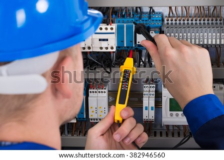 Male Electrician Examining Fusebox With Voltage Tester - stock photo