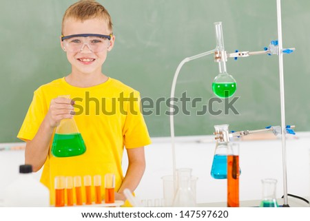 male elementary school student in the lab holding a flask - stock photo