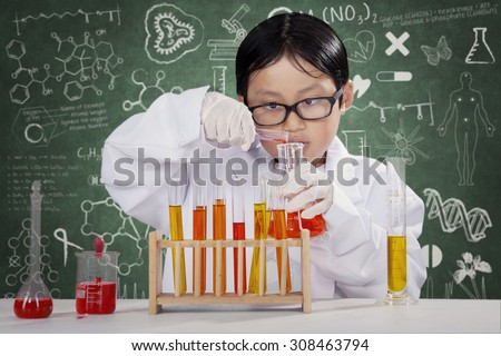Male elementary school student learning chemistry while wearing coat in the lab - stock photo