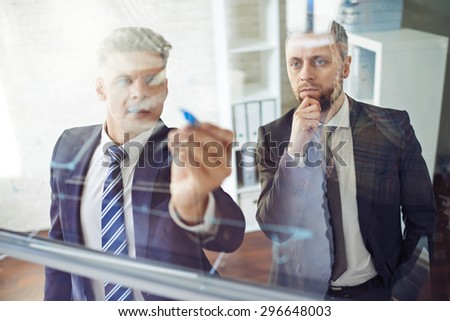 Male employee explaining graph on transparent board