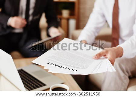 Male employee holding business papers - stock photo