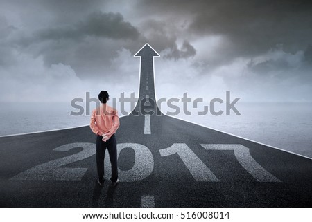 Male employee looking at an upward arrow at the end of a road while standing on the road with number 2017