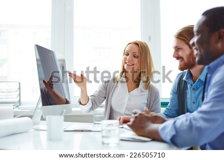 Male employees looking at computer monitor while their female colleague presenting new project - stock photo