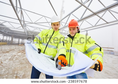 male engeneers construction foreman managers outdoors indoors at building site with blueprints - stock photo