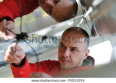 Male engineer at work place, solar panels plant industry in background