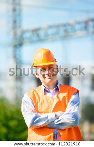male engineer in a helmet on a background of industrial designs