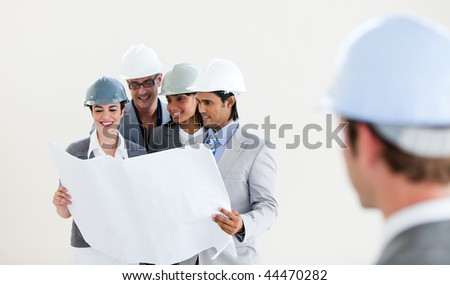 Male Engineer looking back at his smiling colleagues against a white background - stock photo