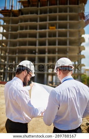 Male engineers discussing sketch of new building