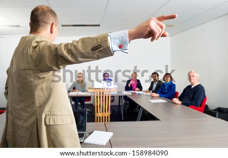 Male entrepreneur giving presentation to colleagues in conference room, focus on the pointing hand - stock photo