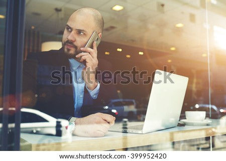 Male entrepreneur is phoning via cell telephone to client after receiving negative reviews on-line via net-book. Businessman is calling via mobile phone, while is sitting with laptop computer in cafe - stock photo