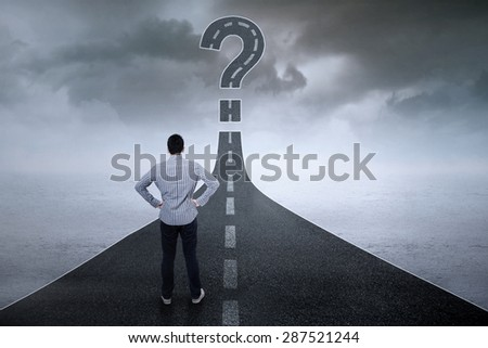 Male entrepreneur standing on the highway while looking at question sign - stock photo