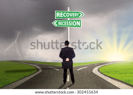 Male entrepreneur standing on the road and look at a signpost while choosing the road to recovery or recession finance - stock photo