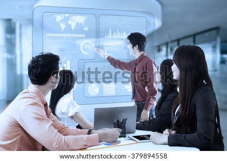 Male entrepreneur using virtual screen to show business solutions and financial graph on his partners