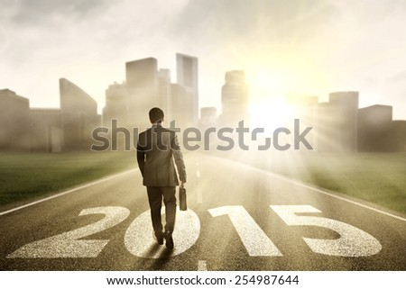 Male entrepreneur walking on the road with numbers 2015 while carrying a briefcase toward a city - stock photo