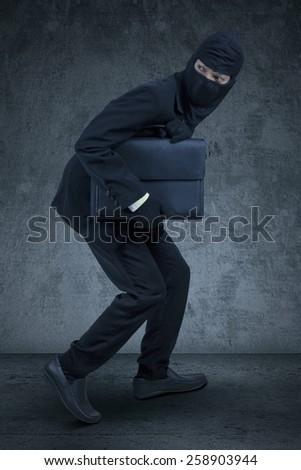 Male entrepreneur wearing a mask and slink to steal a briefcase, shot against dark background - stock photo